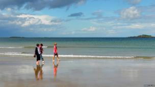 Taking a stroll along the beach in Portrush - by Kenny Allen