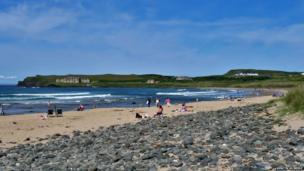 The sun shines over the beach at Portballintrae - by Mervyn McBride