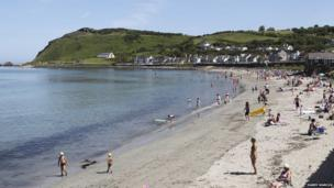 Crowds enjoying the sunshine at Ballygally beach - by Harry Marcus