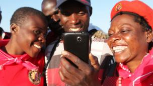 MDC supporters looking an internet site on a mobile phone, Harare, Zimbabwe - Tuesday 9 July 2013