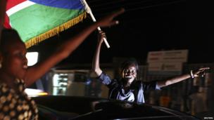 Women, one holding a South Sudanese flag, during independence day celebrations in a car in Juba, South Sudan - Tuesday 9 July 2013