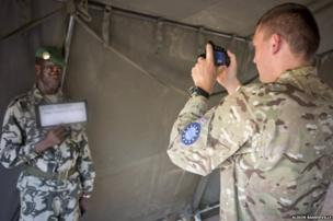 A British soldier photographs a Malian soldier