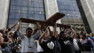 Youths carry the World Youth Day cross as it arrives at Rio de Janeiro city hall, 10 July