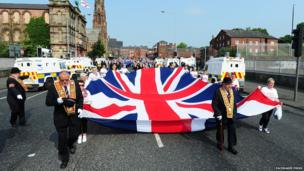 A large Union flag was carried at the front of the parade, as it's made its way to Belfast City Centre.