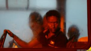A would-be immigrant looks out of a window on a police bus after arriving at the Armed Forces of Malta (AFM) Maritime Squadron base in Valletta