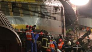 Rescue workers evacuate a victim at the scene the train derailed at Bretigny sur Orge, 13 July 2013