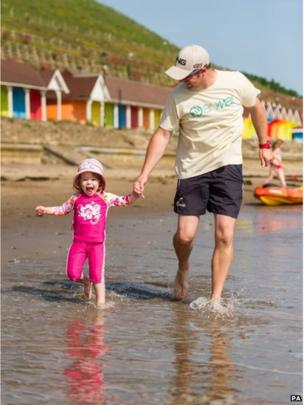 Richard Davis with daughter Ruth (3) enjoying the sun on a beach in Scarborough, North Yorkshire