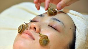 Snails crawl on the face of a woman