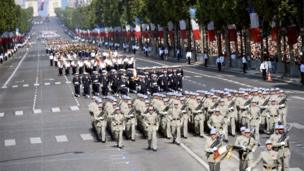 Students of the National School of Active Non-commissioned Officers (front) take part in the Bastille Day parade.