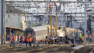 French railway employees and rescue workers inspect the wreckage of a derailed intercity train at the Bretigny-sur-Orge