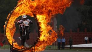 An Indian army soldier performs a motorcycle stunt