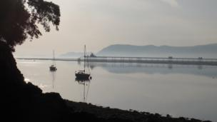 Bangor Pier from the shore of the Menai Strait early on a quiet summer morning. Taken by John Smith of Glyn Garth, Anglesey, from the bottom of the public footpath by Plas Rhianfa.
