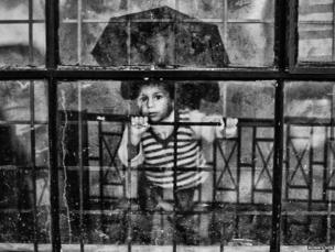 A boy looks from the glass door of the gate of the relief camp in Joshimath.