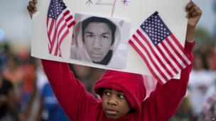 A boy holds a picture of Trayvon Martin during a protest march in Atlanta