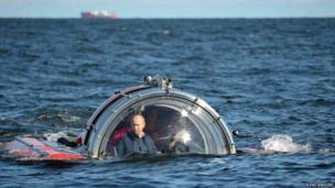 Vladimir Putin in a round mini-submarine type sea-craft.