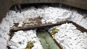 Panamanian workers stand atop sacks of sugar inside a North Korean-flagged ship
