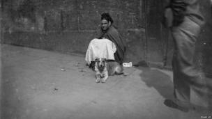 Man walks past a blind woman and her dog, Edgar Lee, c 1892