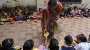 Indian schoolchildren receive their free mid-day meal at a school in Ahmedabad on 17 July 2013
