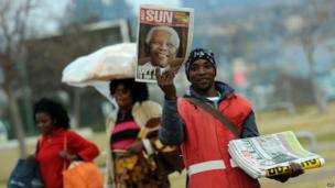 Newspaper vendor holds up paper with Mandela's picture on the front, Soweto (18 July)