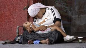 A Syrian refugee holds her child as they doze off in the southern Lebanese city of Sidon