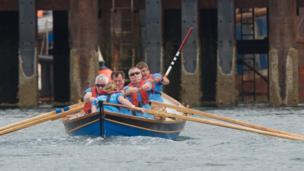 People rowing skiffs