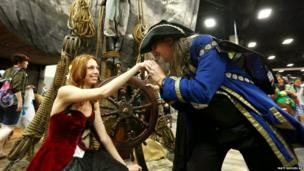 A comic book fan greets a model at the Black Sails booth during the San Diego Comic-Con