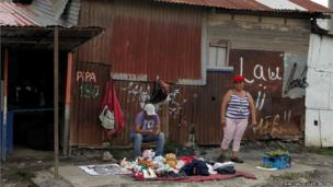 Two women sell clothes and fruit on a street at the La Caprio slum, near San Jose in Costa Rica