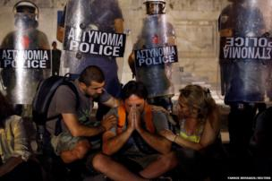 A man is comforted by colleagues in front of a police line guarding the Greek parliament in Athens.