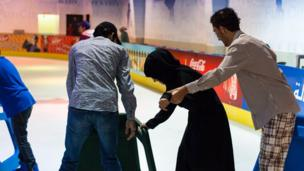 A woman skater being helped to stand on the rink