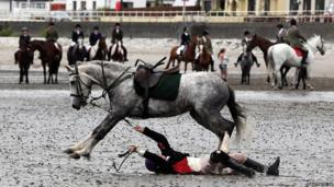 A competitor falls during the beach mounted relay