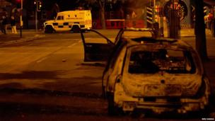 Burnt out cars and a police van on a dark street. Photo: Ben Hanna