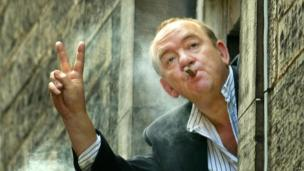 Mel Smith appears smoking a cigar out of a window at the Assembly Halls in Edinburgh