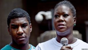 Trayvon Martins mother Sybrina Fulton speaks at a podium as Trayvon Martins brother Jahvaris Fulton (l) stands by during a rally honouring Trayvon Martin organized by the National Action Network outside One Police Plaza in Manhattan 20 July 2013 in New York City.