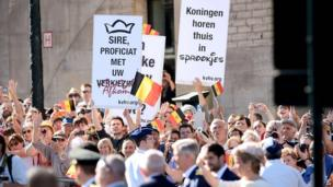 Anti-monarchy students hold up placards in Brussels on 21 July 2013