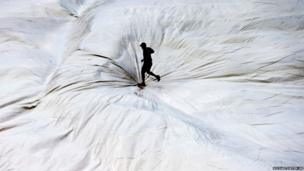 A man walks across a tarpaulin