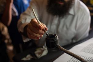 Dipping a quill in the ink