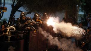 Riot police officers fire tear gas on protesters in Rio de Janeiro. Photo: 22 July 2013