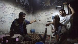 Members of the Free Syrian Army chat as they sit inside a house in Deir al-Zor