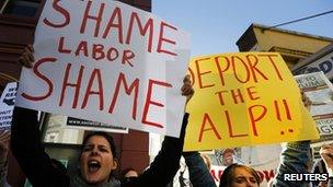Women hold posters bearing messages against the Australian Labor Party (ALP) during a rally in support of asylum seekers outside an ALP meeting in Sydney 22 July 2013