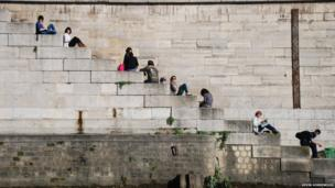 People on steps at the side of the River Seine, Paris