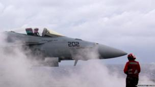 A US Navy F-18 strike fighter aircraft prepares to take off from the deck of the USS George Washington