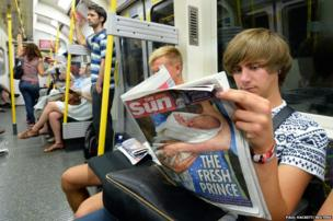 A tube passenger reads a copy of The Sun newspaper