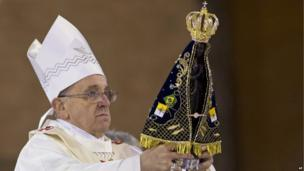 Pope Francis holds up the statue of Our Lady of Aparecida, Brazil's patron saint, during Mass in the Aparecida Basilica