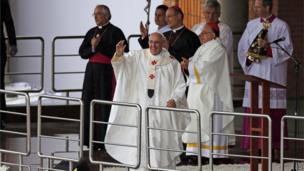 Pope Francis waves to pilgrims attending Mass outside the Aparecida Basilica in Aparecida, Brazil, Wednesday, July 24, 2013