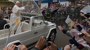 Pope Francis waves at the faithful from the Popemobile after giving a mass at the Basilica of Our Lady of Aparecida