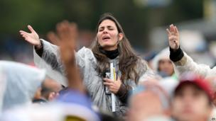 A woman prays during a Mass celebrated by Pope Francis outside the Aparecida Basilica