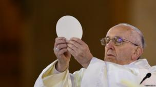 Pope Francis holds communion as he celebrates Mass at the Basilica of the Shrine of Our Lady Aparecida