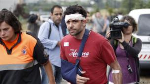 A man with head bandage and right arm in a sling accompanied by a rescue worker