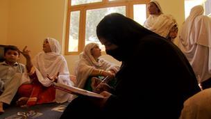 A woman in a burqa sitting down