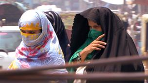 Two women with their faces covered walking in a crowded street